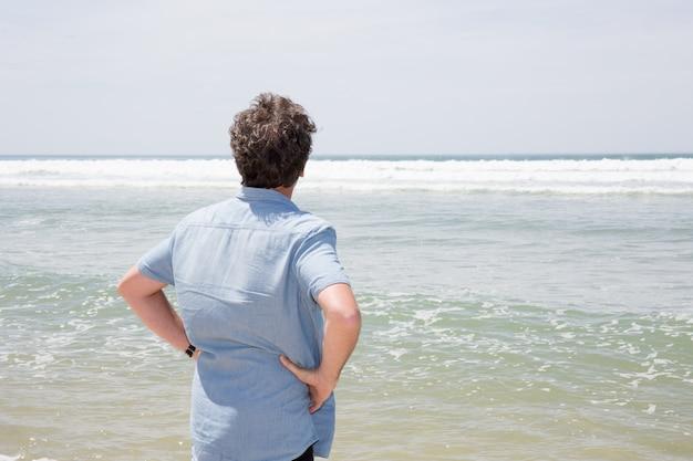 Achteraanzicht van de mens alleen op strand zomer