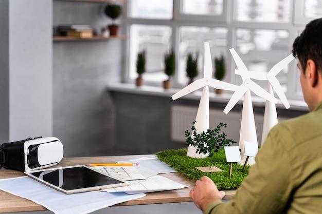 Achteraanzicht van de mens die aan een milieuvriendelijk windenergieproject werkt