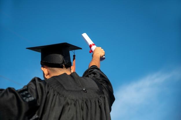 Achteraanzicht van de mens die handen een certificaat en pet in de lucht gooit, graduatiedag op de hemelachtergrond