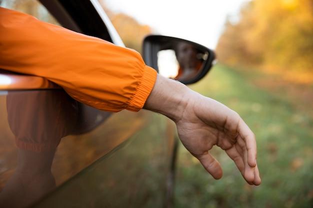 Achteraanzicht van de mens die zijn hand uit de auto haalt tijdens een roadtrip