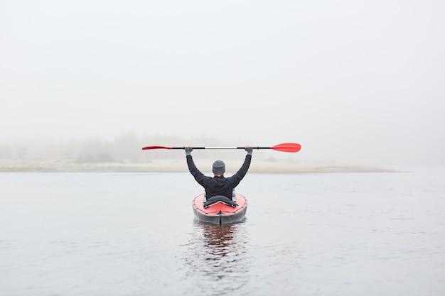 Achteraanzicht van de mens in kajak op rivier met opgeheven riem