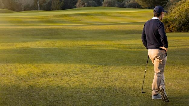 Achteraanzicht van de mens op het met gras begroeide golfveld met kopie ruimte