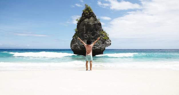 Achteraanzicht van de mens voor rotsachtig eiland met tropische vegetatie, prachtig uitzicht bewonderend, staande op het strand met azuurblauwe oceaanwater en blauwe lucht op de horizon