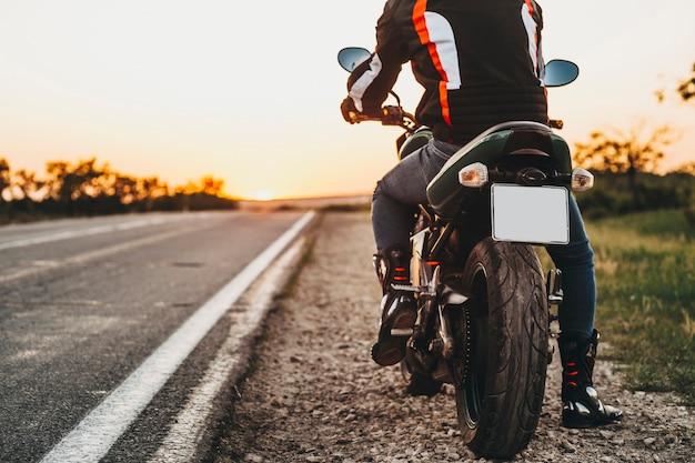 Achteraanzicht van de motorfiets aan de kant van de weg terwijl de fiets onderweg is voor het reizen met de fiets tegen zonsopgang.