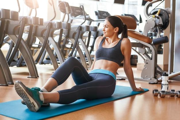 Achteraanzicht van de training van een korte en slanke jonge vrouw in sportkleding die in de sportschool staat