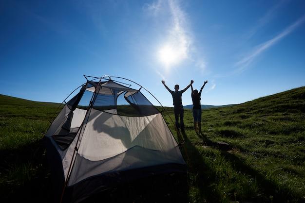 Achteraanzicht van de twee mensen staken hun handen omhoog naar het zonlicht op een groen gras in de bergen bij de camping. het concept van actieve zomervakantie op de camping