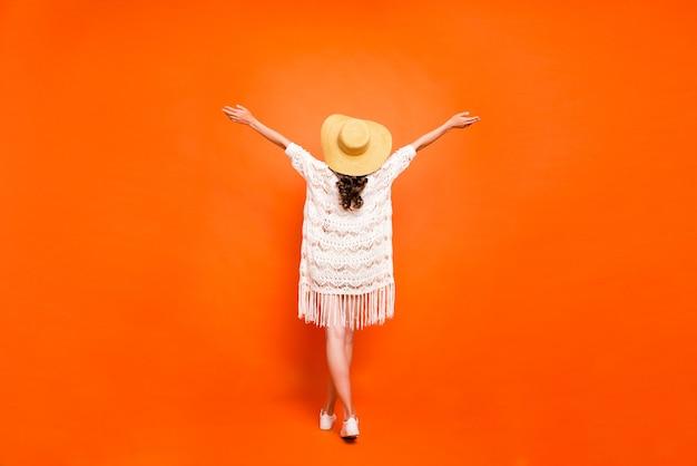 Achteraanzicht van de volledige lengte van de zomervakantie van de dame die handen opheft, draag een lichte witte kanten strandmantel van de zonnehoed.