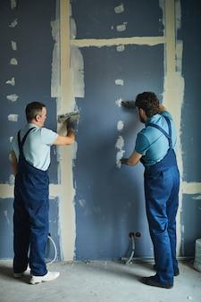 Achteraanzicht van de volledige lengte van twee bouwvakkers droge muur bouwen tijdens het renoveren van huis, kopie ruimte