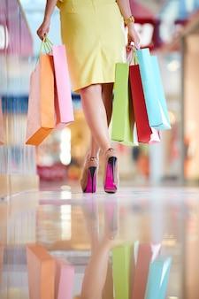 Achteraanzicht van de vrouw bedrijf boodschappentassen