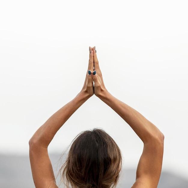 Achteraanzicht van de vrouw die buiten yoga doet
