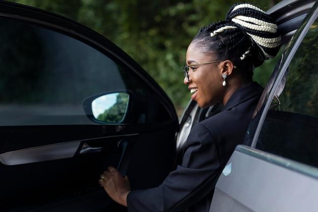 Achteraanzicht van de vrouw die uit haar gloednieuwe auto komt