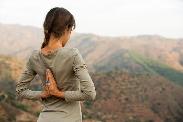 Achteraanzicht van de vrouw die yoga doet terwijl ze het uitzicht op de natuur bewondert