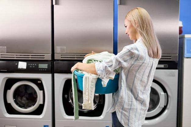 Achteraanzicht van de vrouw kwam om kleren te wassen in het washuis, stond alleen te wachten, met een wasbak met een enorme stapel dingen