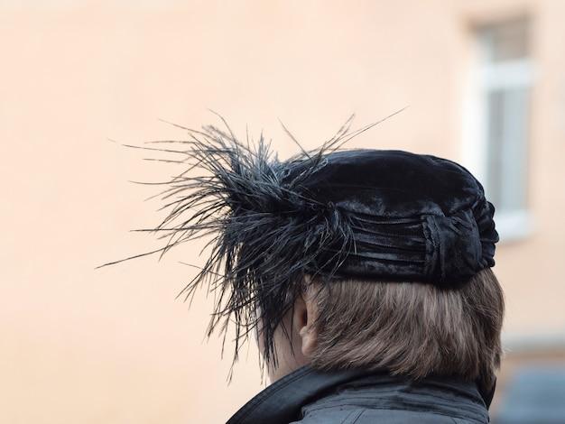 Achteraanzicht van de vrouw met zwarte hoed met veren op het hoofd in een open lucht.