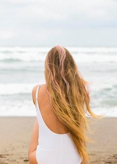 Achteraanzicht van de vrouw op het strand met kopie ruimte