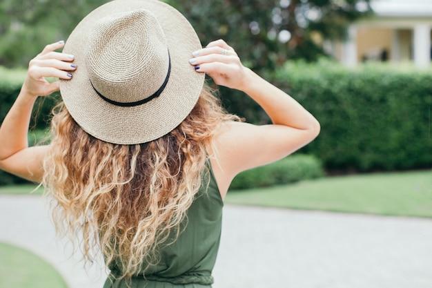 Achteraanzicht van de vrouw van de de zomermode met groene kleding en strohoed die zich op landelijke achtergrond bevinden.