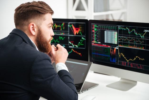 Achteraanzicht van doordachte, bebaarde jonge zakenman die zit en wakker wordt met grafiek en grafieken op de computer