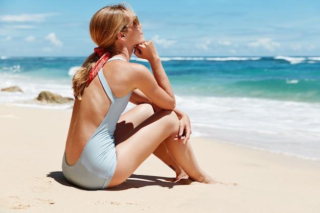 Achteraanzicht van doordachte vrouw overweegt terwijl zit op zand in de buurt van de oceaan, draagt blauwe bikini en zonnebril
