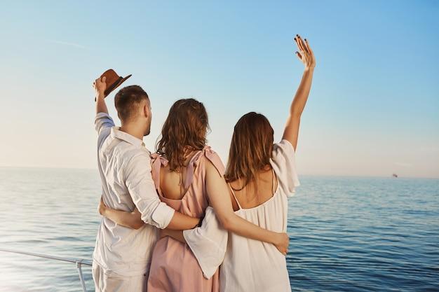 Achteraanzicht van drie beste vrienden reizen per boot knuffelen en zwaaien terwijl u op zee kijkt. mensen die op luxe vakantie zijn, zeggen hallo tegen crue die per jacht passeert.
