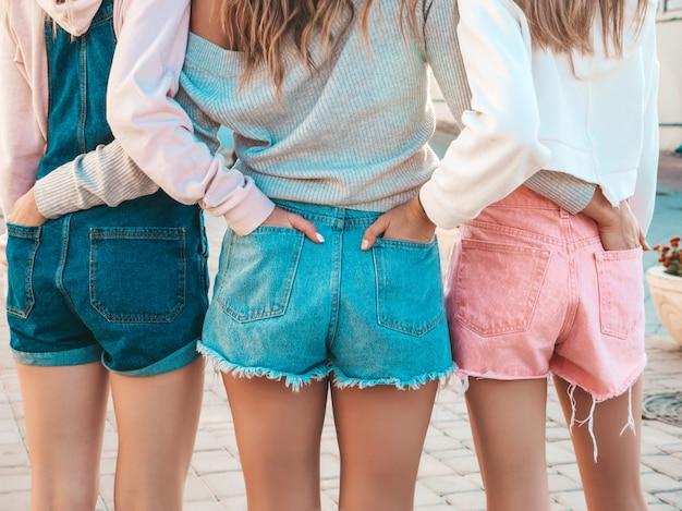Achteraanzicht van drie jonge vrouwelijke hipster vrienden. meisjes gekleed in zomer casual kleding. vrouwen buitenshuis staan. ze staken hun handen in korte broek in achterzakken. poseren bij zonsondergang