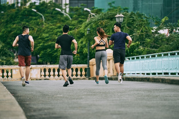 Achteraanzicht van drie man en een meisje joggen samen op een zomerdag