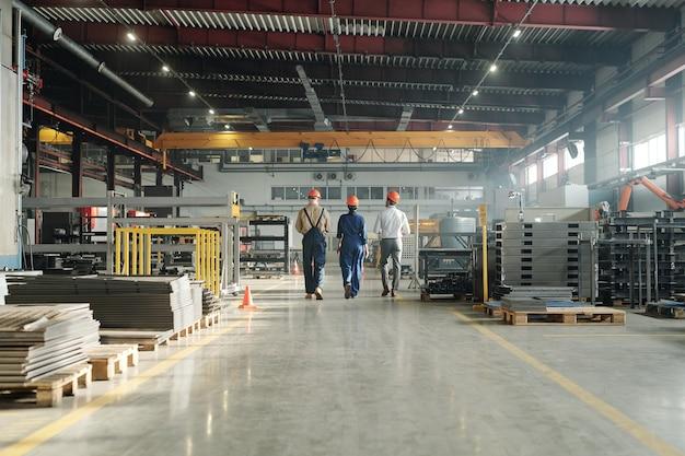 Achteraanzicht van drie technici of ingenieurs van industriële installaties in werkkleding die de werkplaats aan het einde van de werkdag verlaten