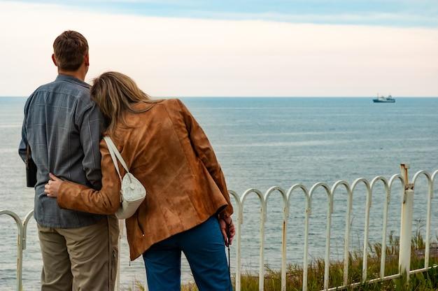 Achteraanzicht van echtpaar man en vrouw knuffelen en kijken in de verte naar de horizon van de zee.