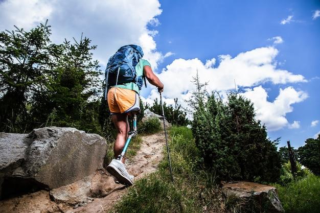 Achteraanzicht van een actieve mannelijke toerist die geniet van nordic walking terwijl hij een gezonde manier van leven leidt
