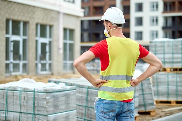 Achteraanzicht van een arbeider met een veiligheidshelm en een beschermend masker die voor de bouwmaterialen staat