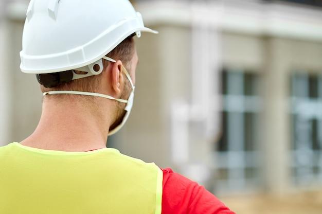 Achteraanzicht van een arbeider met een veiligheidshelm en een beschermend masker op de bouwplaats
