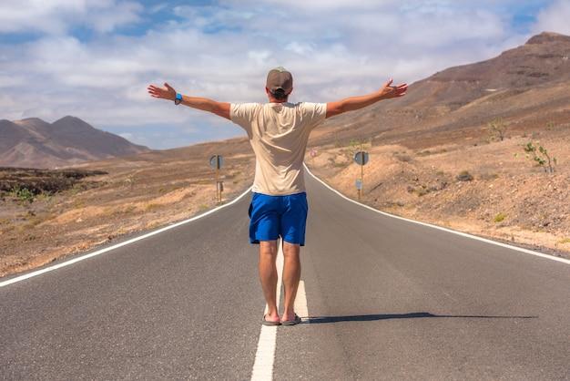 Achteraanzicht van een avontuurlijke man die op de weg naar pozo negro staat met zijn handen in de lucht