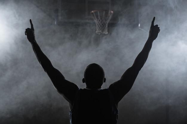 Achteraanzicht van een basketbalspeler met zijn armen in de lucht