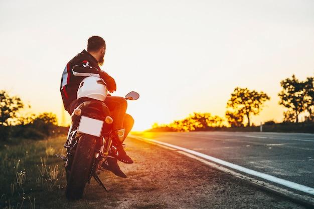 Achteraanzicht van een bebaarde fietser zittend op zijn motorfiets zittend en kijkend naar de zonsondergang aan de kant van de weg tijdens het reizen met de fiets tegen zonsondergang.