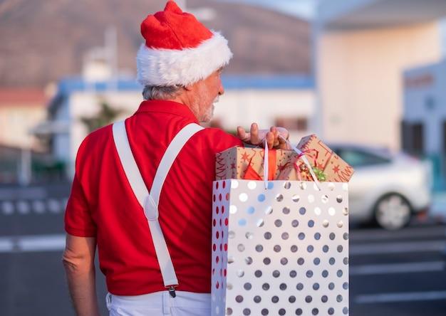 Achteraanzicht van een bejaarde grootvader tijdens het winkelen voor kerstmis met een kerstmuts en bretels