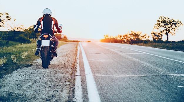 Achteraanzicht van een blanke man die goed uitgerust begint te rijden op een motorfiets met een zonsondergang op de achtergrond