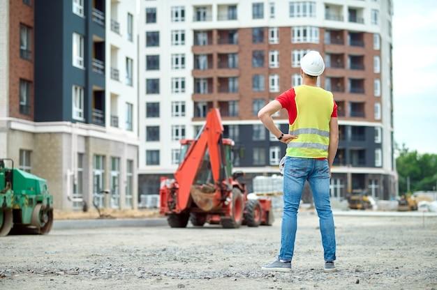 Achteraanzicht van een bouwer gekleed in een reflecterend vest en een veiligheidshelm die voor een graafmachine op de bouwplaats staat