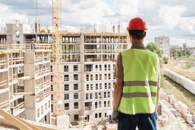 Achteraanzicht van een bouwvakker die een veiligheidshelm draagt terwijl hij in een hoogbouw kopieerruimte staat
