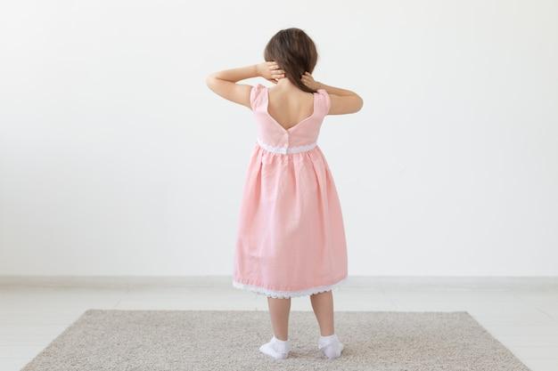 Achteraanzicht van een charmant klein meisje prinses in een roze jurk poseren in een designer jurk op een wit oppervlak
