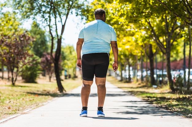 Achteraanzicht van een dikke en zwaarlijvige man die in het park loopt
