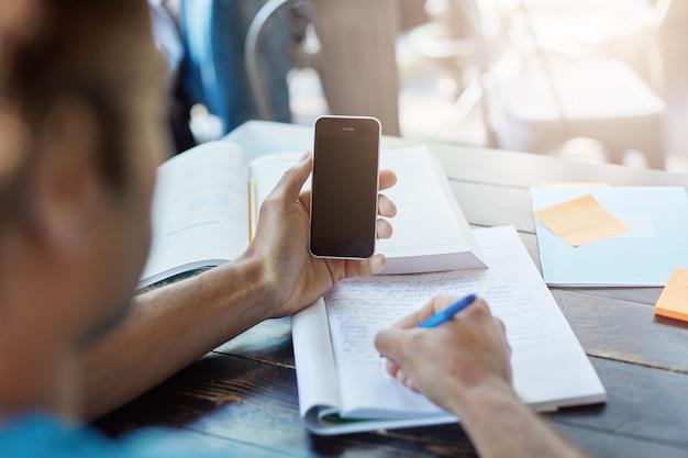 Achteraanzicht van een donkere student die slimme telefoon met leeg scherm vasthoudt voor uw informatie, notities in schrift opschrijft tijdens het leren in de universiteitsbibliotheek of kantine