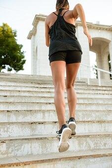 Achteraanzicht van een fitness vrouw in koptelefoon
