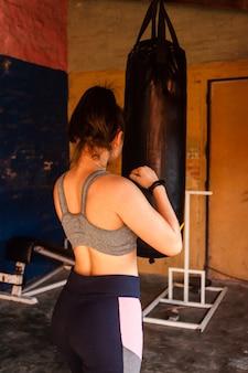 Achteraanzicht van een fitnessmeisje klaar om de bokszak te raken.
