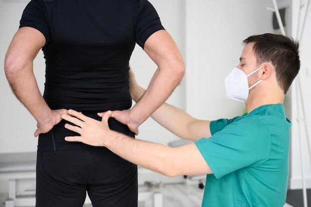 Achteraanzicht van een fysiotherapeut die man terug onderzoekt.