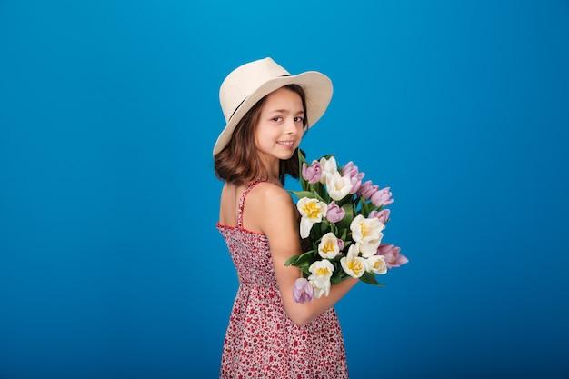 Achteraanzicht van een gelukkig mooi klein meisje met een boeket bloemen op een blauwe achtergrond
