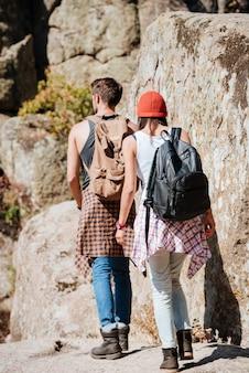 Achteraanzicht van een gelukkig paar wandelaars wandelen en hand in hand