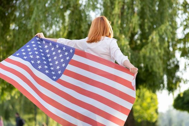 Achteraanzicht van een gelukkige jonge roodharige vrouw die poseert met de nationale vlag van de v.s. die buiten staat