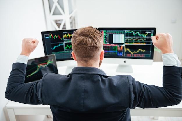 Achteraanzicht van een gelukkige succesvolle zakenman die met opgeheven handen zit en met de computer op kantoor werkt