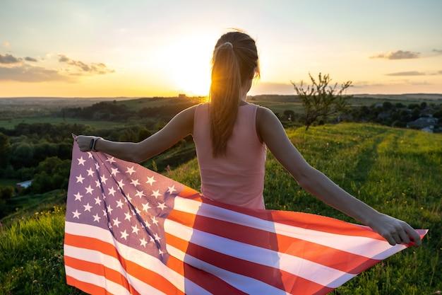 Achteraanzicht van een gelukkige vrouw met de nationale vlag van de vs die buiten staat bij zonsondergang.