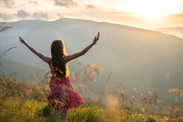 Achteraanzicht van een gelukkige vrouw wandelaar in rode jurk staande op met gras begroeide heuvel op een winderige avond in de herfst bergen met uitgestrekte armen genieten van uitzicht op de natuur bij zonsondergang.