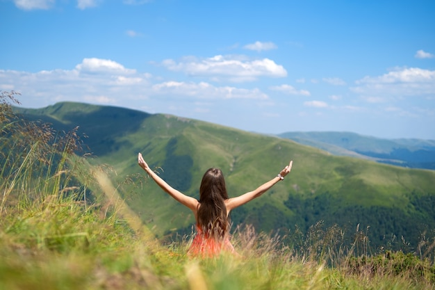 Achteraanzicht van een gelukkige vrouw wandelaar in rode jurk zittend op een met gras begroeide heuvel op een winderige dag